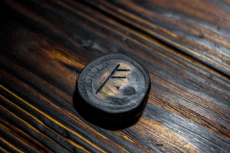 Rune Fehu van hout op een houten achtergrond wordt gesneden die royalty-vrije stock afbeelding