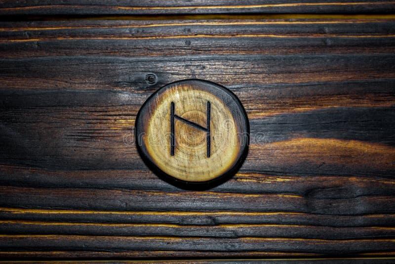 Rune Haglaz Hagalaz van hout op een houten achtergrond wordt gesneden die royalty-vrije stock fotografie