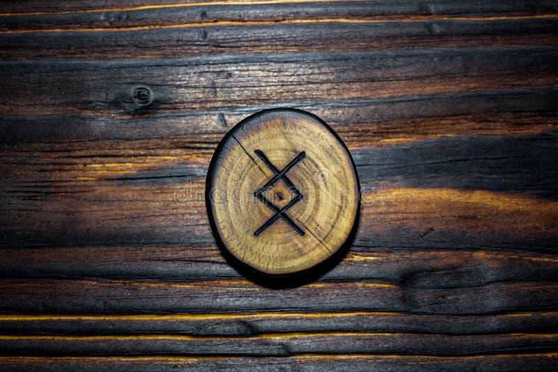 Rune Ingwaz Yngvi a découpé du bois sur un fond en bois photos stock