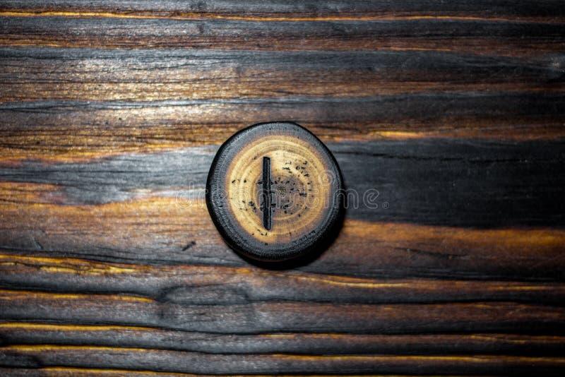 Rune Isaz Isa schnitzte vom Holz auf einem hölzernen Hintergrund lizenzfreie stockbilder