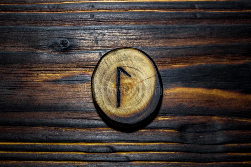 Rune Laguz Laukaz, Lagu carved from wood on a wooden background. Elder Futhark royalty free stock images