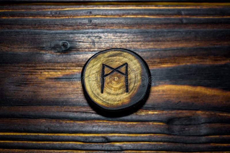 Rune Mannaz Mann cinzelou da madeira em um fundo de madeira foto de stock royalty free