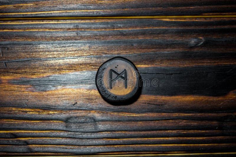 Rune Mannaz Mann cinzelou da madeira em um fundo de madeira foto de stock