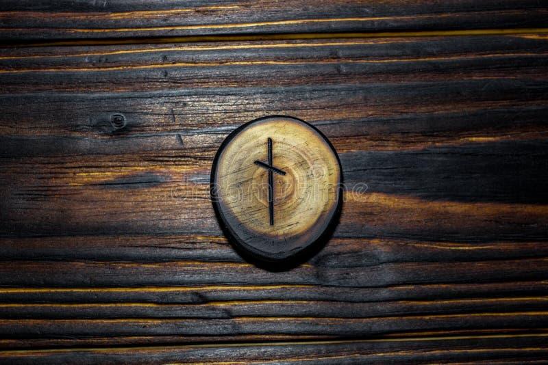 Rune Naudiz schnitzte vom Holz auf einem hölzernen Hintergrund stockfoto