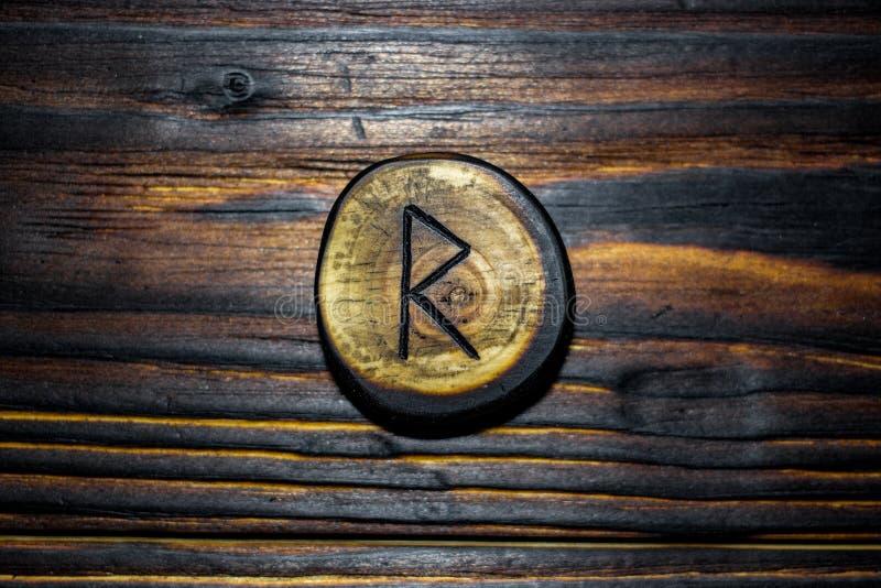 Rune Raido van hout op een houten achtergrond wordt gesneden die stock foto's