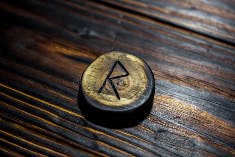Rune Raido van hout op een houten achtergrond wordt gesneden die stock afbeeldingen