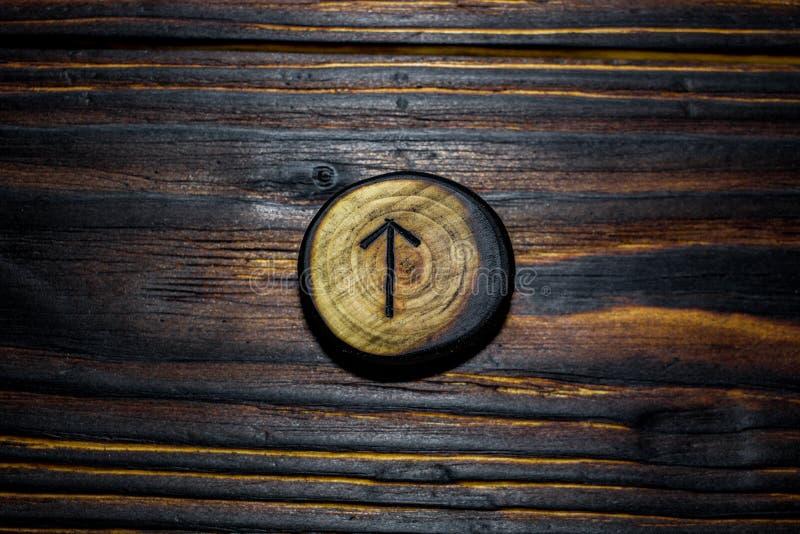 Rune Tiwaz Tyr van hout op een houten achtergrond wordt gesneden die stock fotografie