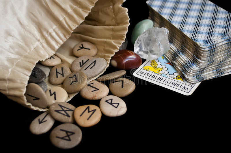 Runes and tarot cards. Divination and prediction on runes and Tarot, mysticism or esoteric isolated on black background stock photos