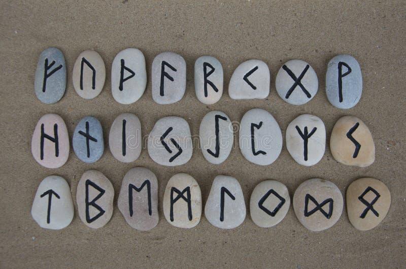 Runiczny abecadło na rzeźbiących kamieniach nad piaskiem fotografia stock