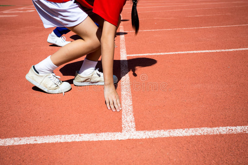 runing在轨道的孩子在体育场内 库存照片