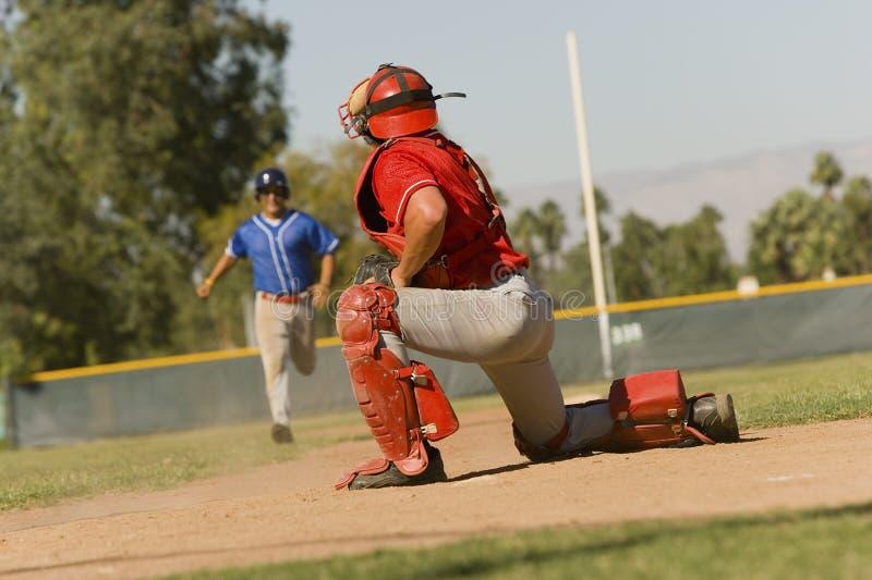 Runner Approaching Catcher On Field. Baseball runner approaching catcher on field during match stock photos