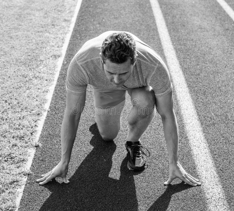 Runner athlete concentrated low start position. Runner take part competitions low start position. Focused on sport goal. Ready to achieve victory. Man athlete royalty free stock photos