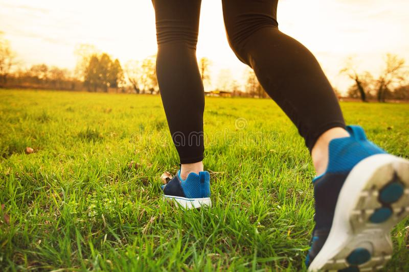 Runner athlete feet. Running on grass.Male fitness sunlight jogging workout. Sport athlete active lifestyle concept.Athletic pair of legs running on grass royalty free stock photo