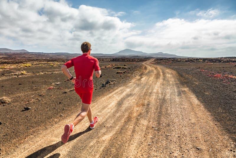 Runner athlete running in mountain trail. Fit man training cardio outdoors. Summer sport fitness run in desert. Landscape stock photo