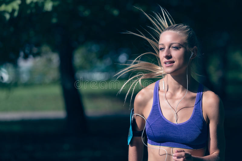 Runner athlete running at park. woman fitness jogging workout wellness concept. Runner athlete running at tropical park. woman fitness jogging workout wellness royalty free stock images