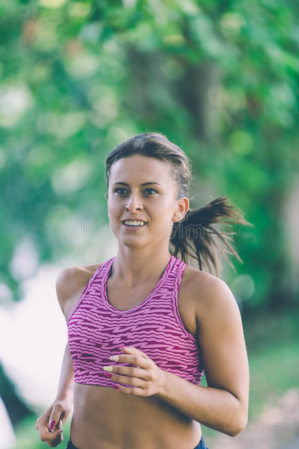 Runner athlete running at park. woman fitness jogging workout wellness concept. royalty free stock image