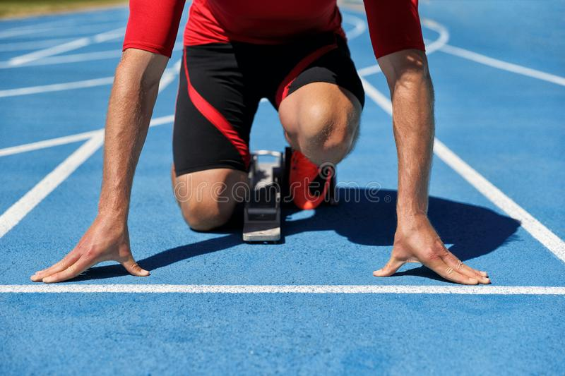 Runner athlete starting running at start of run track on blue running tracks at outdoor athletics and fiel stadium. Sport and stock photos