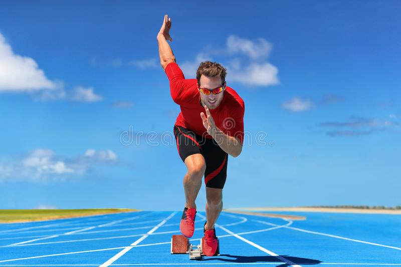 Runner athlete starting running at start of run track on blue running tracks at outdoor athletics and fiel stadium. Sprinter on. Race. Sport and fitness man royalty free stock photography