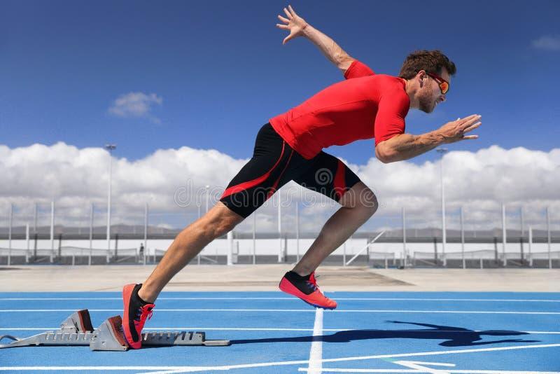 Runner athlete starting running at start of run track on blue running tracks at outdoor athletics and fiel stadium. Sprinter. Sport and fitness man running stock photo