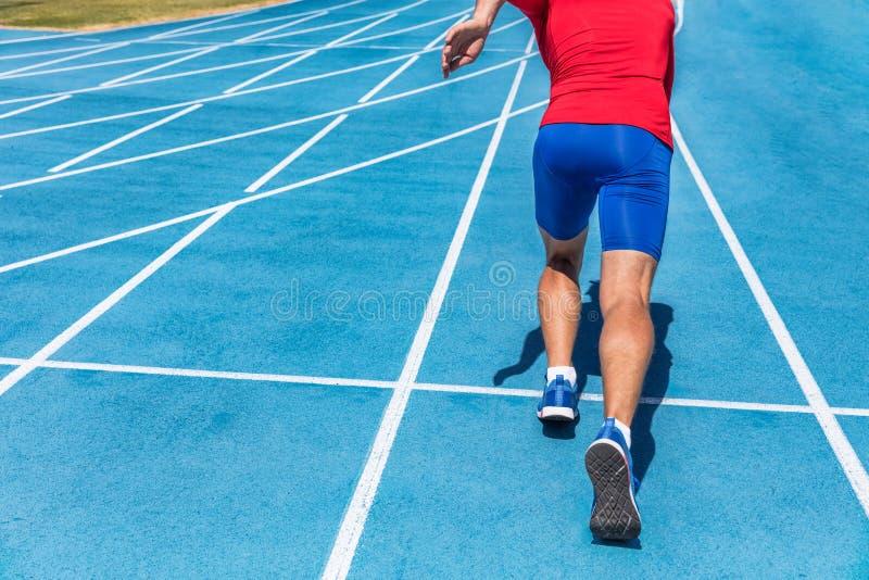 Runner athlete starting running at start of run track on blue running tracks at outdoor athletics and fiel stadium. Sprinter. Sport and fitness man lower body stock images