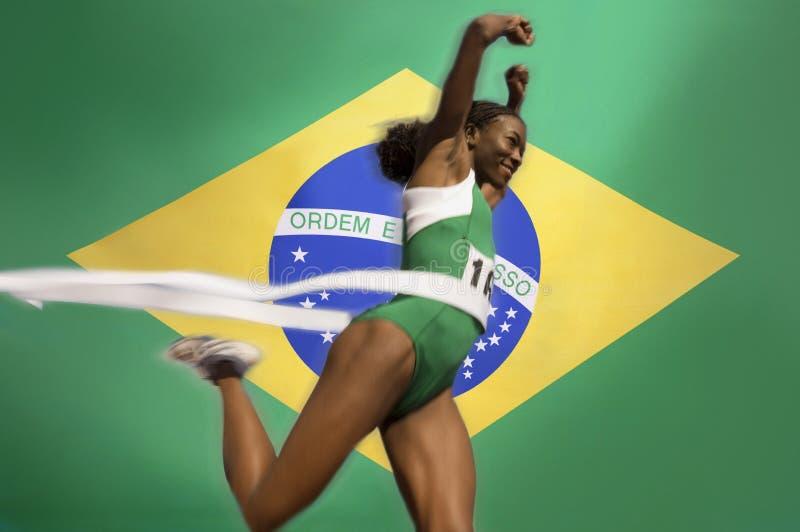Runner Breaking through the finishing line tape over Brazilian flag stock photography