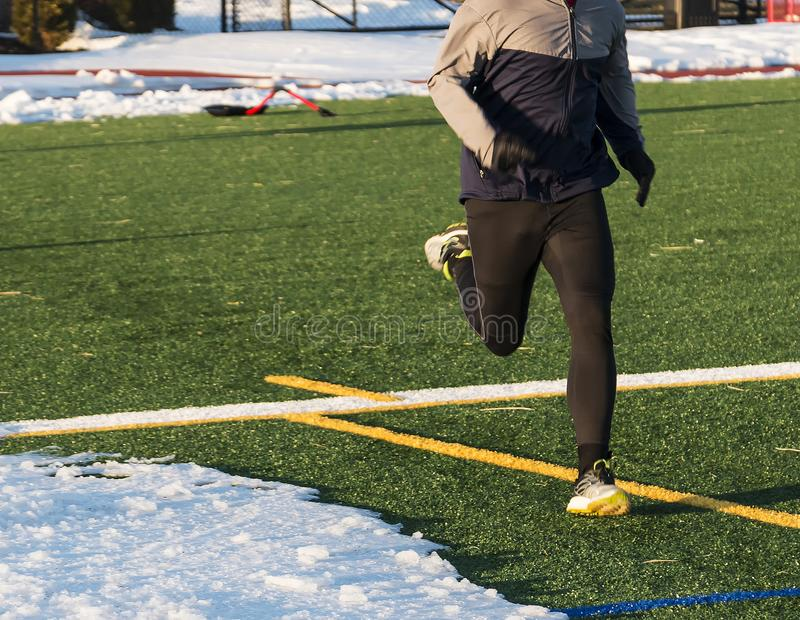 Runner on turf field with snow royalty free stock photos