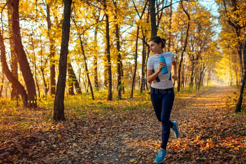 Runner exercising in autumn park. Woman running with water bottle at sunset. Active healthy lifestyle royalty free stock photo
