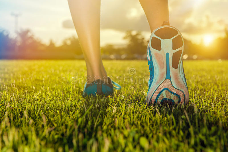Runner feet practice running on grass. Closeup on shoe. Fitness and workout wellness concept royalty free stock image