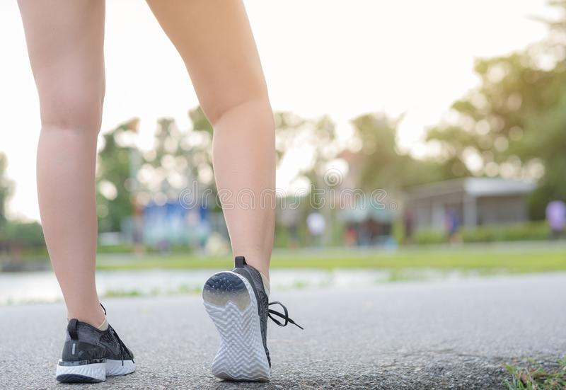 Runner feet running on road closeup leg on shoe. woman fitness sunrise jog workout wellness concept royalty free stock photo