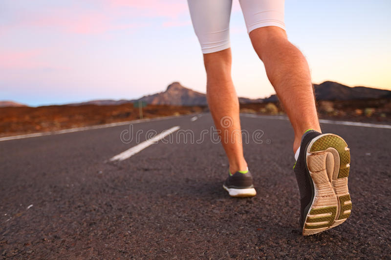 Runner feet running on road closeup on shoe. Man fitness athlete jogger workout in wellness concept at night stock photography