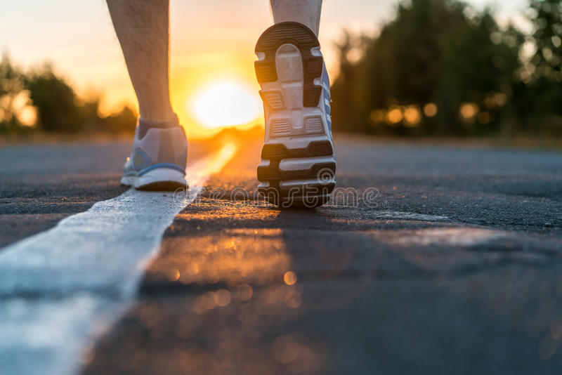 Runner feet running on road closeup. On shoe. man fitness sunet jog workout welness concept on sunrise royalty free stock photos