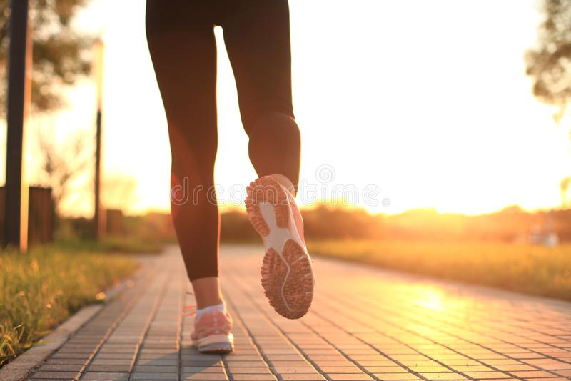 Runner feet running on road closeup on shoe, outdoor at sunset or sunrise. Runner feet running on road closeup on shoe, outdoor at sunset or sunrise royalty free stock photo