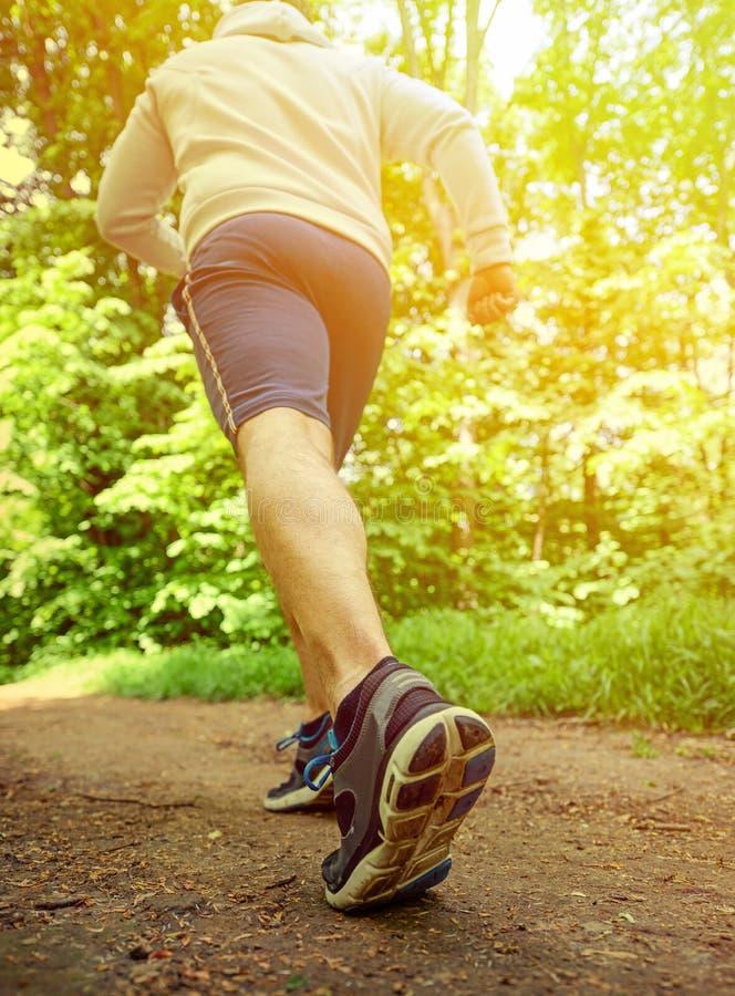 Runner feet running on road closeup on shoe. Conceptual shot stock photo