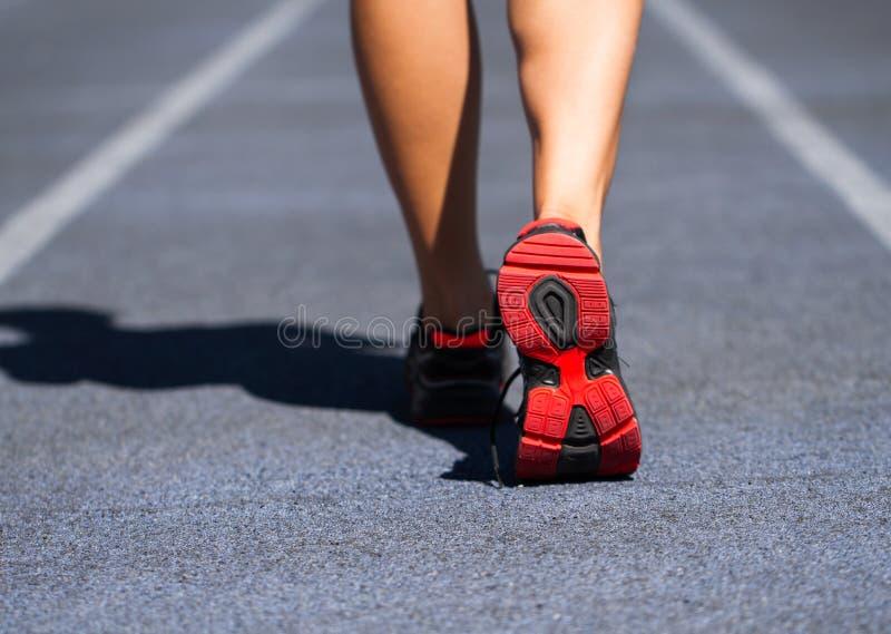 Runner feet running on road closeup on shoe. Woman fitness jog w. Runner feet running on road closeup on shoe at stadium. Woman fitness jog workout welness stock photography