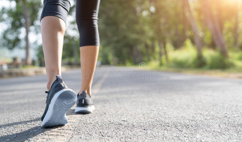 Runner feet running on road closeup on shoe. Woman fitness sunrise jog workout wellness concept. Young fitness woman runner athlet. E running at road royalty free stock photography