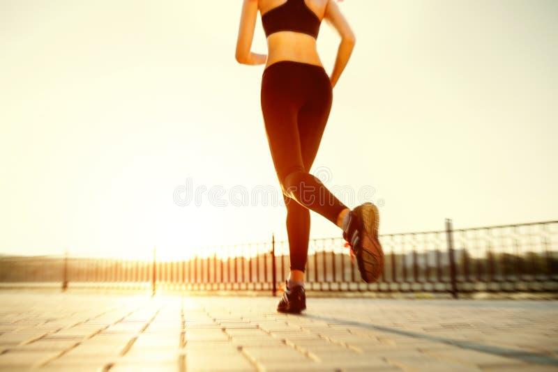 Runner feet running on road closeup on shoe. Woman fitness sunrise jog workout welness concept stock images