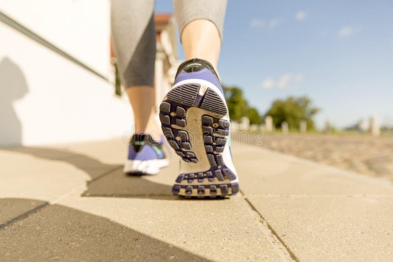 Runner feet running on road closeup on shoe. woman fitness sunrise jog workout welness concept royalty free stock image