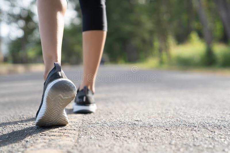 Runner feet running on road closeup on shoe. Woman fitness sunrise jog workout welness concept. Young fitness woman runner athlete stock image