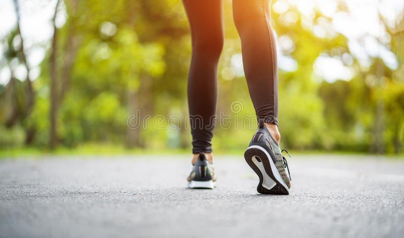 Runner feet running on road closeup on shoe. Young fitness woman runner athlete running at road. Athlete runner feet running on ro. Ad closeup on shoe. Woman stock photo