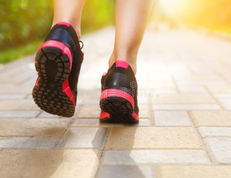 Runner feet running on road closeup on shoes. Woman fitness sunrise jog workout welness concept stock photos