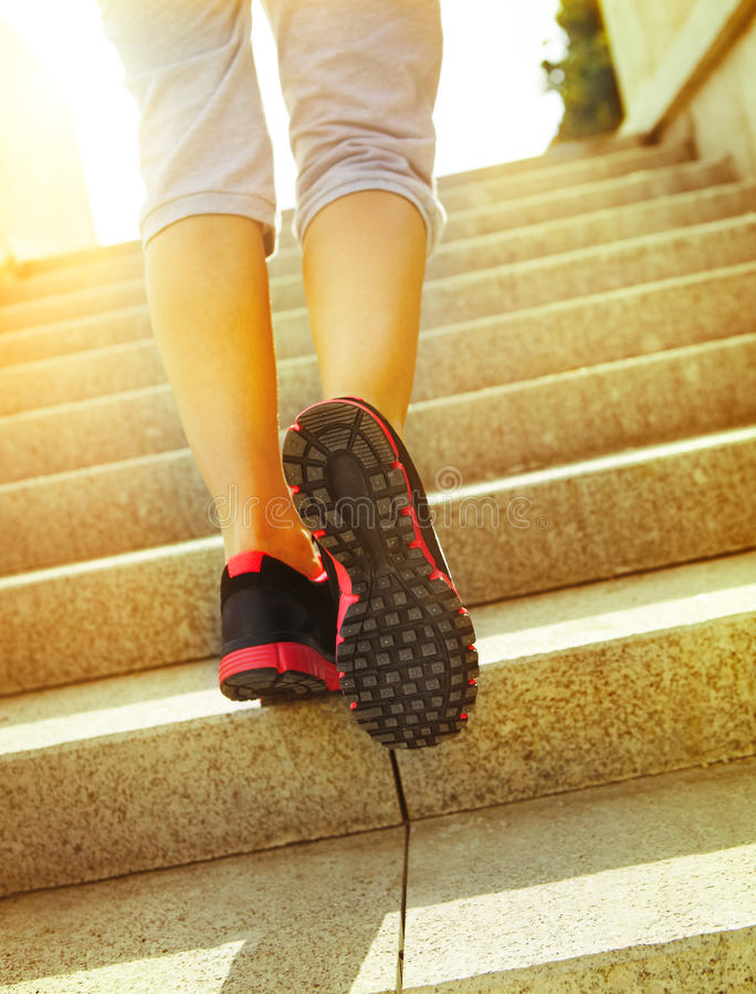 Runner feet running on road closeup on shoes. Woman fitness sunrise jog workout welness concept royalty free stock photography