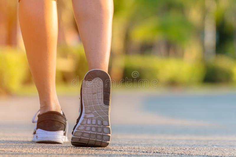 Runner feet running on the road in the outdoor workout park, closeup on shoe. Asian fitness woman running for healthy and relax. stock photos