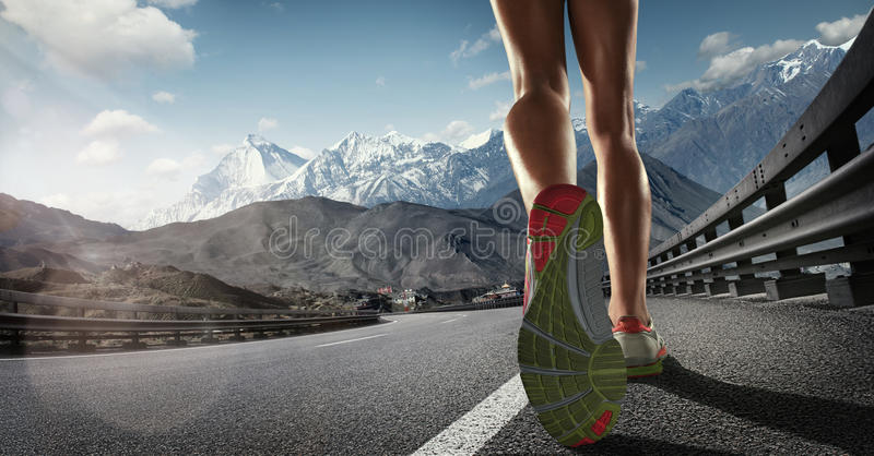 Runner feet running on road. Sports background. Runner feet running on road closeup on shoe royalty free stock image