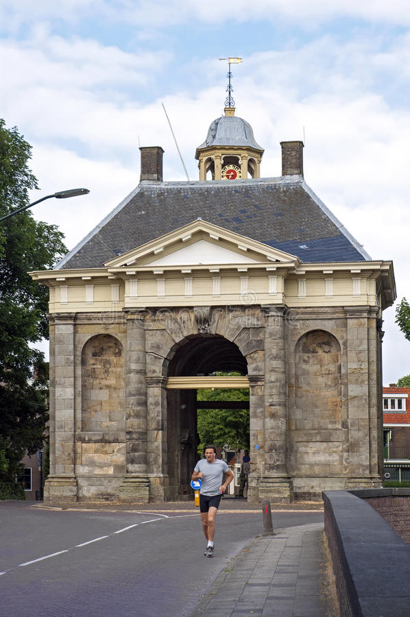 Runner in front of ancient city gate in Enkhuizen. Netherlands, province Noord-Holland, area, region West Friesland, city, fortified Enkhuizen: the Koepoort or royalty free stock photos