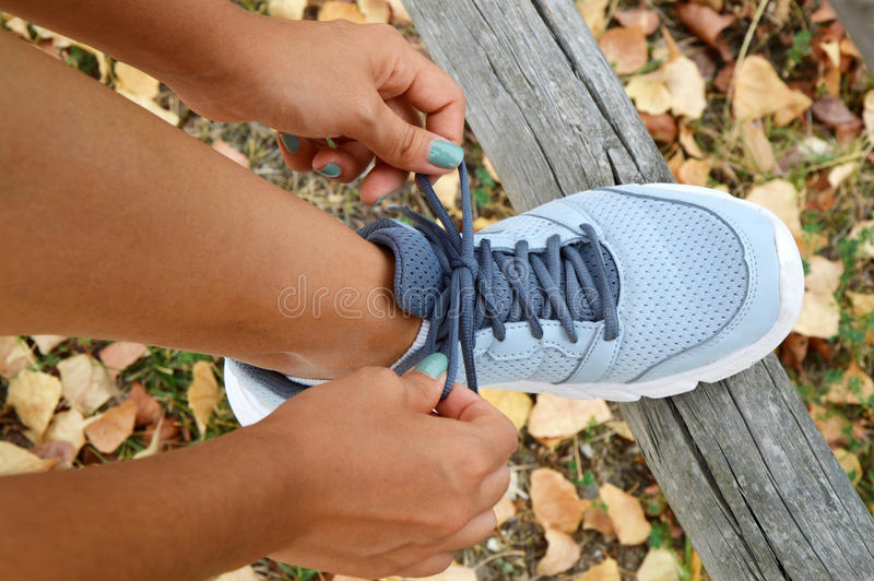 Runner getting ready for jogging tying running shoes laces, POV. Girl preparing before run stock photos