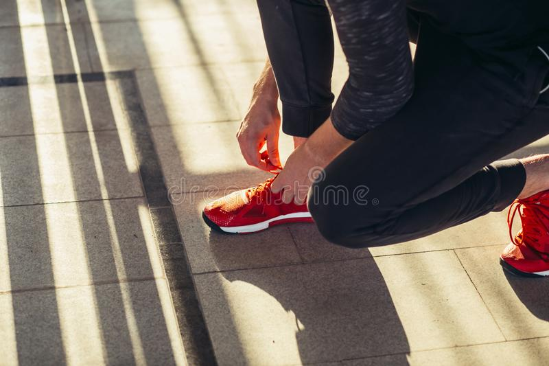 Runner getting ready jogging tying running shoes laces while sitting on track. Runner getting ready for jogging tying running shoes laces while sitting on track royalty free stock images