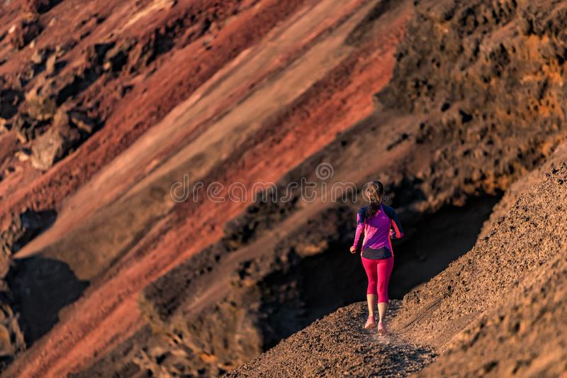Runner girl training running on volcano mountain side trail. Young woman on ultra run athlete doing cardio fitness workout. Healthy and active lifestyle royalty free stock photo