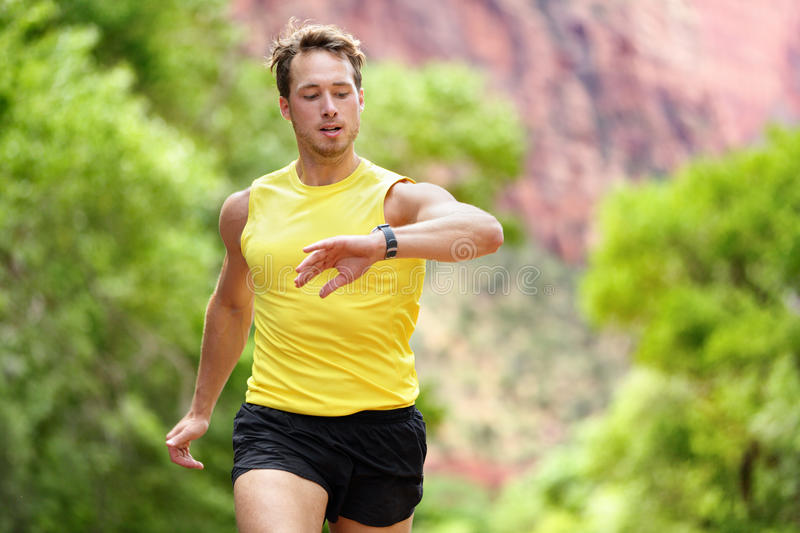 Runner looking at heart rate monitor smartwatch. While running. Man jogging outside looking at his sports smart watch during workout training for marathon run royalty free stock photography
