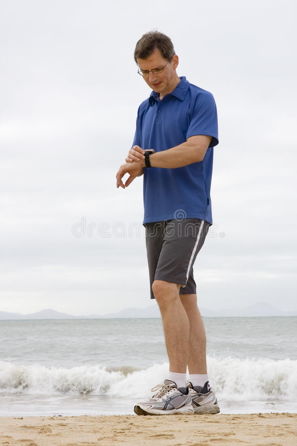 Runner looking at stop watch. On a beach royalty free stock image