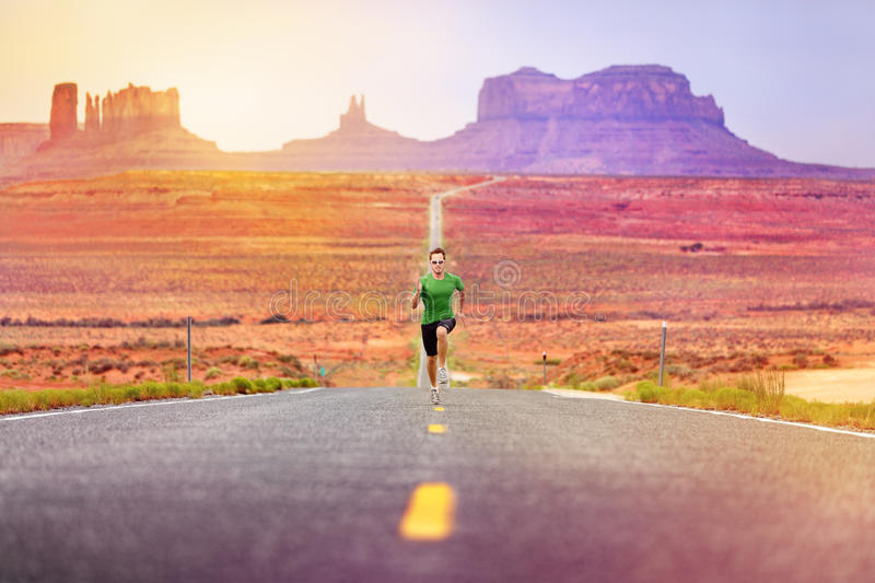 Runner man athlete running on road Monument Valley. Runner man athlete running sprinting on road by Monument Valley. Concept with sprinter fast training for royalty free stock photography